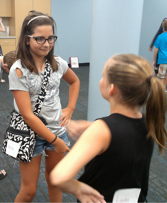 Fifth-year camper Bella, facing, practices mirroring techniques with veteran camper Lanie