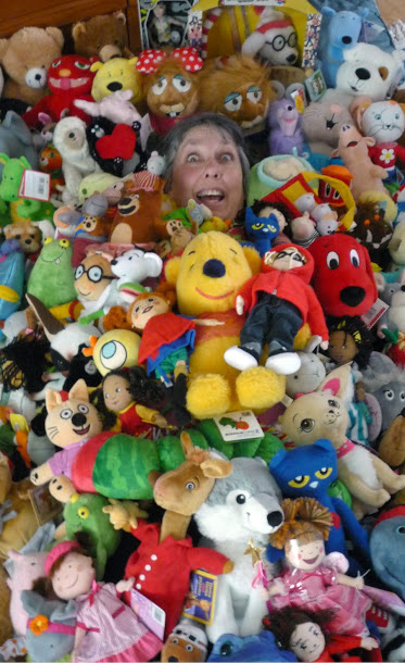 Stephanie Bange in a large pile of dolls and stuffed animals.