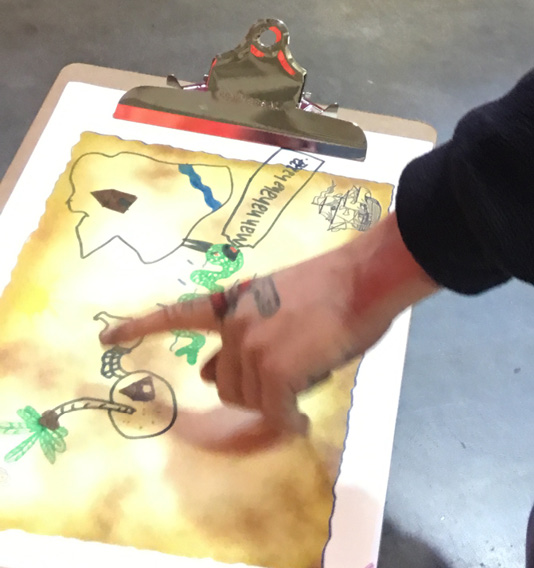 A person pointing to an aspect of a hand-drawn map