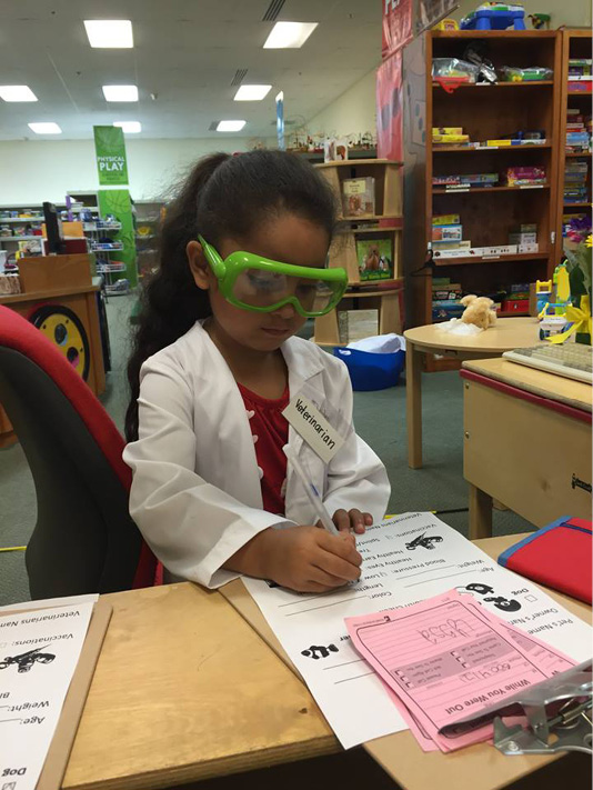 I girl wearing a lab coat and protective goggles