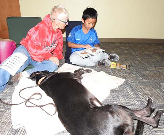 A child working with a therapy dog at Sachem Public Library in Holbrook, New York.