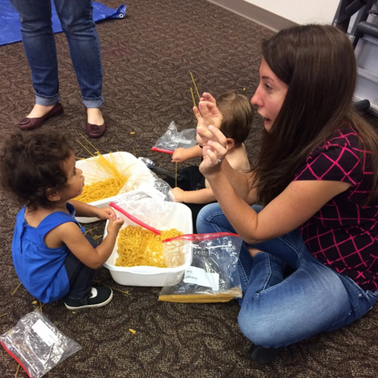 A librarian and small child play with dry noodles.