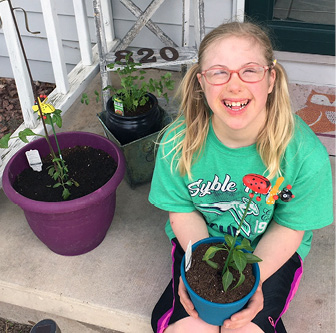Holland Verbeten along with her vegetable seedlings—part of mom Sharon's attempt at science class during the pandemic!