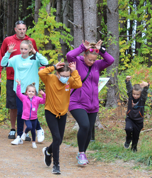 A Gorham family incorporates suggested movements while enjoying the StoryWalk; note this was photographed prior to the outdoor mask mandate in the area.